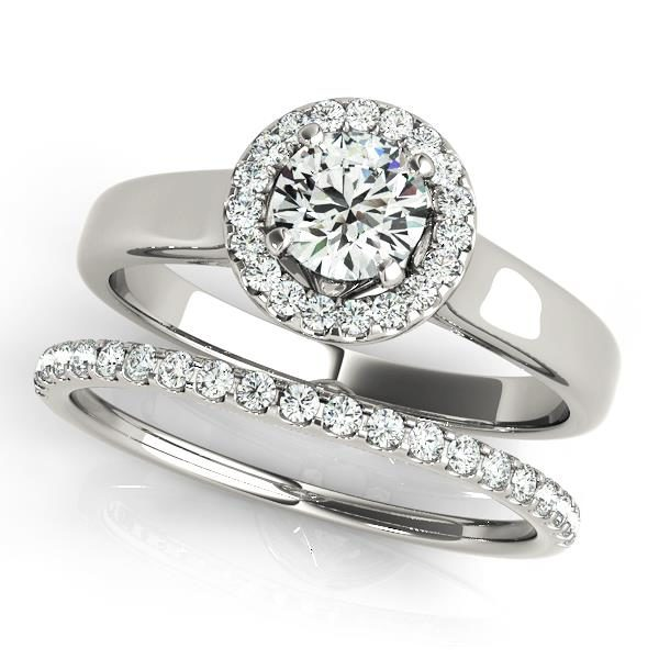 Wedding set of a round halo engagement ring in a plain band and a wedding band with row of small diamonds on upper part of the shank in white gold