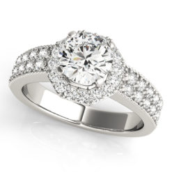 Round cut diamond in a four-pronged setting surrounded by a diamond halo with a paved halo setting in a white cold twisted engagement ring