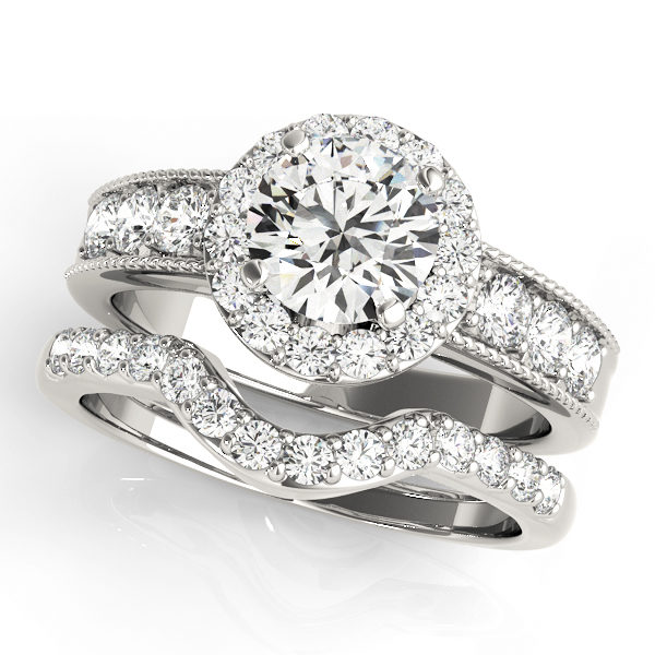 Wedding ring set made of white gold consisting of a round halo engagement ring with a surface prong set side accents and a surface prong set wedding band with a curved centre fitting the shape of the engagement ring