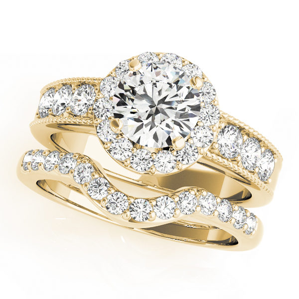 Wedding ring set made of yellow gold consisting of a round halo engagement ring with a surface prong set side accents and a surface prong set wedding band with a curved center fitting the shape of the engagement ring