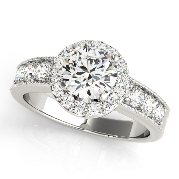 White gold engagement ring with round halo design and surface prong set side accents on the band