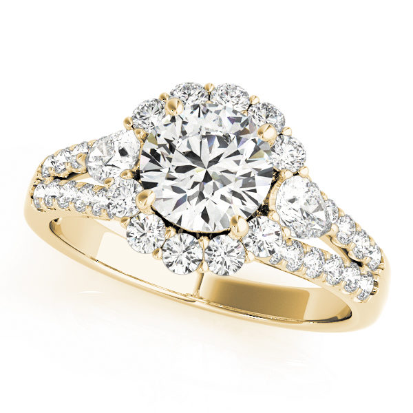 Halo round engagement ring with two pear shaped diamonds each side of the center diamond with row of small diamonds embedded on split shank in yellow gold