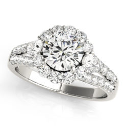 Halo round engagement ring with two pear shaped diamonds each side of the center diamond with row of small diamonds embedded on split shank in white gold