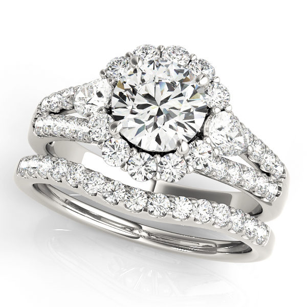 Halo round engagement ring with row of small diamonds embedded on split shank and diamond wedding band in white gold