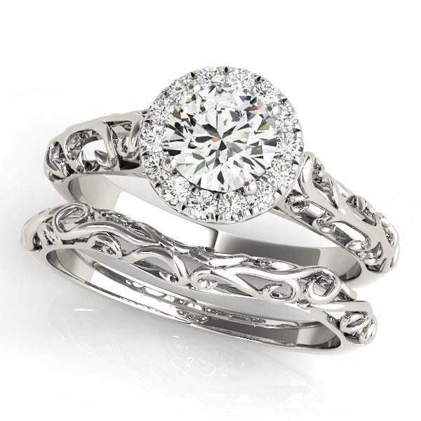 Wedding set made of white gold with two rings an engagement ring with halo and filigree design and a curved filigree wedding band