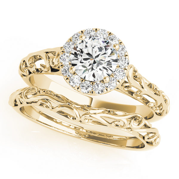 Wedding set made of yellow gold with two rings an engagement ring with halo and filigree design and a curved filigree wedding ban
