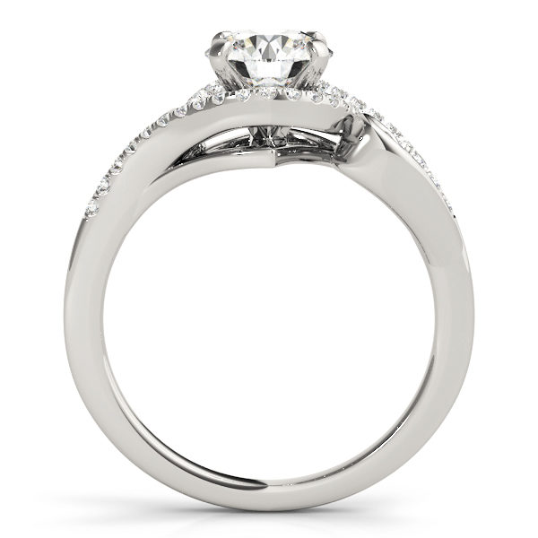 A side view of a white gold engagement ring with round centre cut jewel and diamonds engraved in the band.