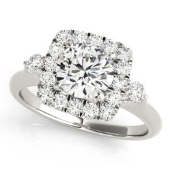 A front view of white gold engagement ring with a round centre cut jewel and halo of diamonds on the side and shoulders.