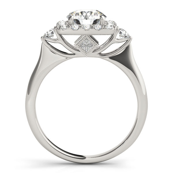 A side view of white gold engagement ring with a round centre cut jewel and halo of diamonds on the side and shoulders.