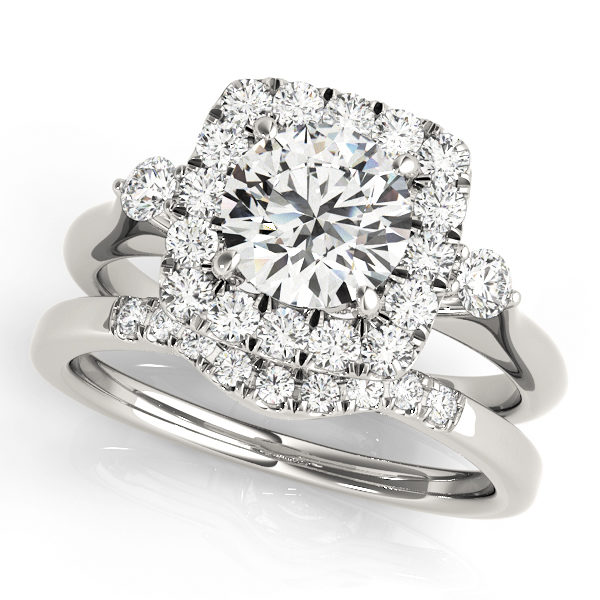A side view of white gold wedding set with a centre cut jewel and halo of diamonds on the side and shoulders.