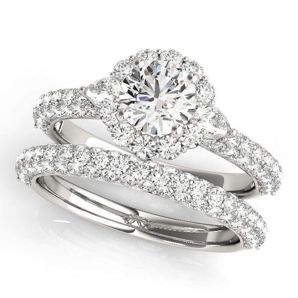 White gold wedding ring set compirsed of a diamond halo 4 prong engagement ring with pave set bands, and a pave set wedding band.