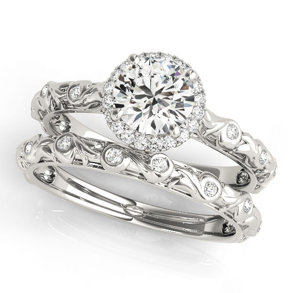 top view of a single center stone halo engagement ring with swirl design shank and a swirl wedding band in white gold