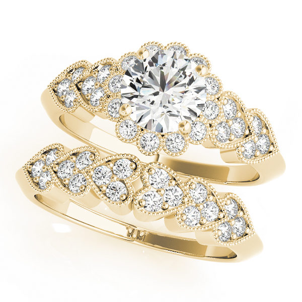 top view of a hearts round halo engagament ring and a heart wedding band in yellow gold