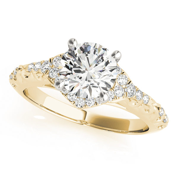 A diamond engagement ring with a centre piece held in place by four white gold prongs, and a halo design surrounding it, with an engraved filigree yellow gold band.