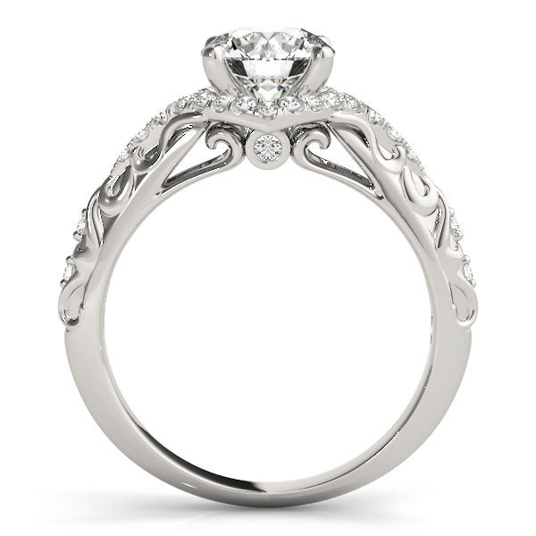 Side view of an engagement ring, with a white gold prong head surrounded by a diamond halo set, and a white gold band with an engraved filigree design.