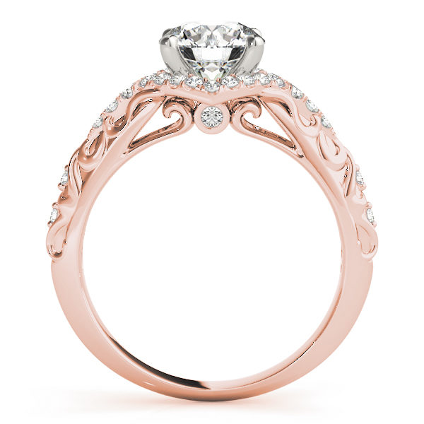 Side view of an engagement ring, with a white gold prong head surrounded by a diamond halo set, and a rose gold band with an engraved filigree design.