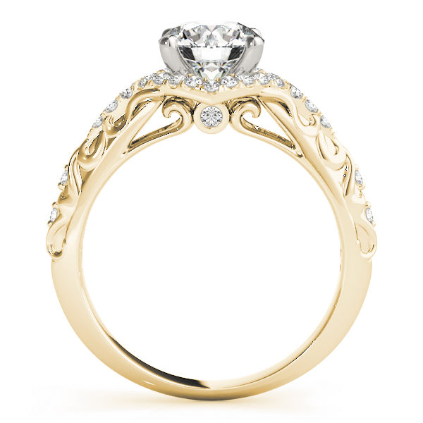 Side view of an engagement ring, with a white gold prong head surrounded by a diamond halo set, and a yellow gold band with an engraved filigree design.