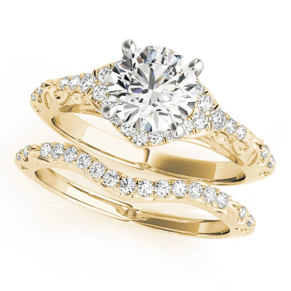 A yellow gold wedding set made up of a halo diamond set engagement ring with an engraved band design, and a curved engraved wedding ring band, embedded with pave set diamonds.