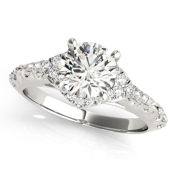 A diamond engagement ring with a centre piece held in place by four white gold prongs, and a halo design surrounding it, with an engraved filigree white gold band.