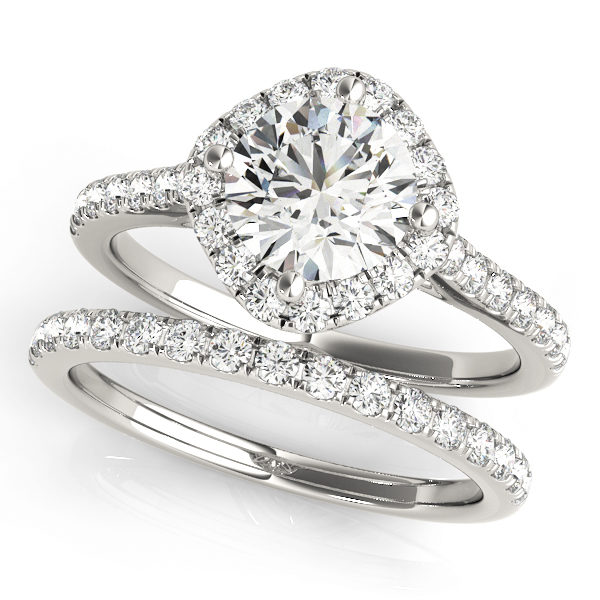 A wedding ring set made of white gold, and consists of a halo style engagement ring with a diamond-shaped base, with an embellished band; and a diamond studded wedding band.