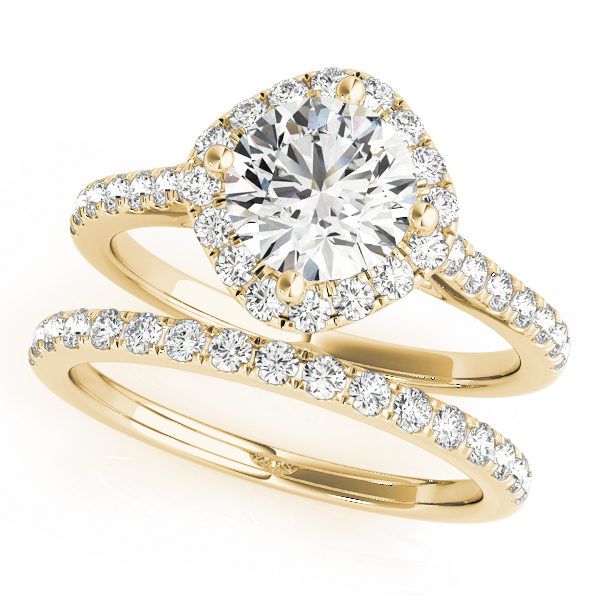 A wedding ring set made of yellow gold, and consists of a halo style engagement ring with a diamond-shaped base, with an embellished band; and a diamond studded wedding band.