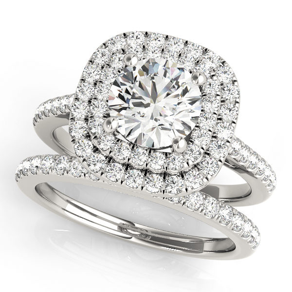 A wedding ring set made of white gold set; which consists of a double halo diamond engagement ring and a diamond studded wedding band, set against a white backdrop.