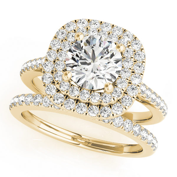 A wedding ring set made of yellow gold set; which consists of a double halo diamond engagement ring and a diamond studded wedding band, set against a white backdrop.