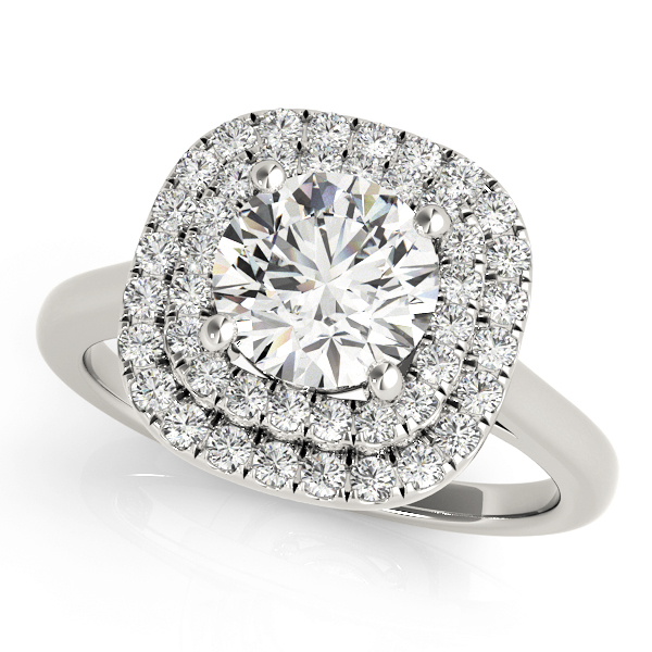 A double halo engagement ring with a large diamond centre piece set on a plain white gold band placed against a white backdrop