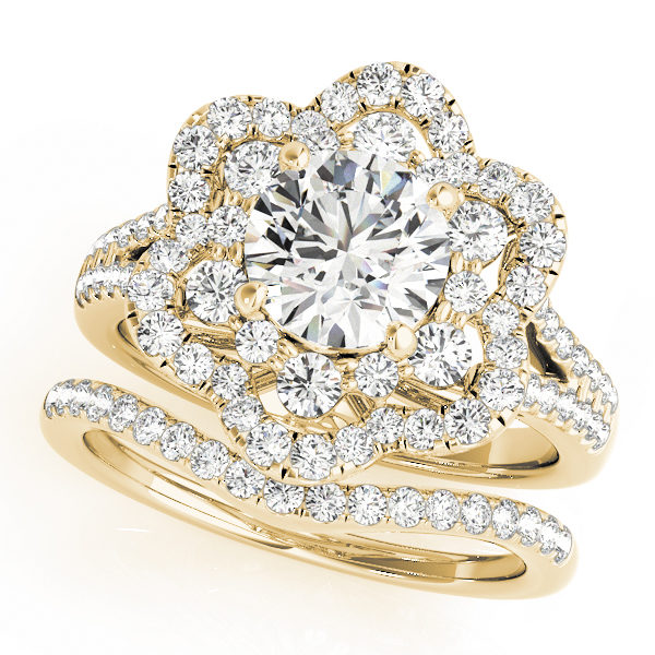 top view of a flower halo diamond engagement ring and a wedding band in yellow gold