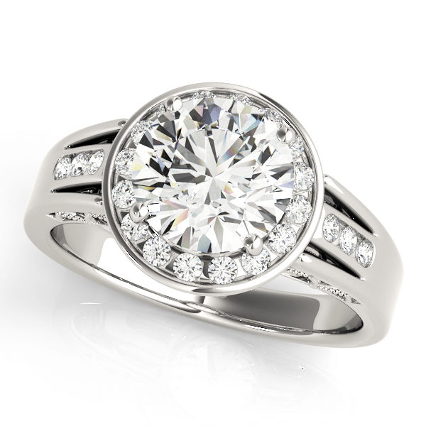 A white gold engagement ring with a large diamond centerpiecem surrounded by a channel set halo, and a tri-band upper shank.