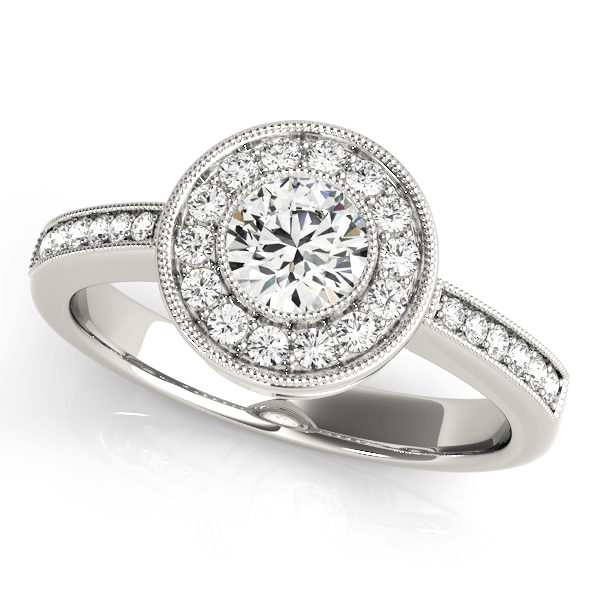A single band white gold engagement ring with a large round halo diamond head surrounded by prong set small diamonds.