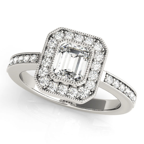 A halo diamond engagement ring in white gold with an emerald cut stone on a pinpointed setting embedded with melee diamonds.