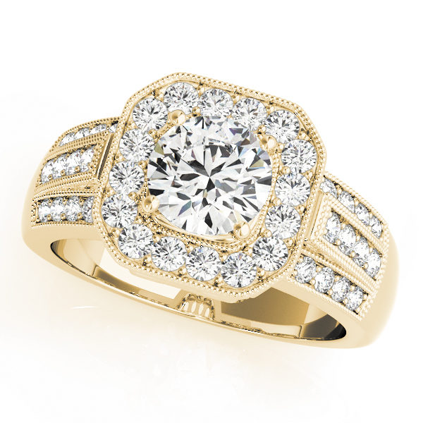 A 4 pronged halo diamond engagement ring in yellow gold with a channeled setting embedded with melee diamonds.