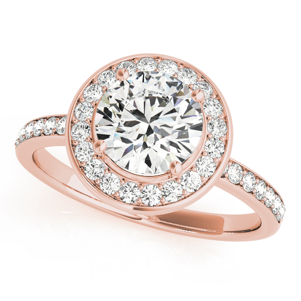A 4 pronged knife-edged halo diamond engagement ring in rose gold with a round cut stone on a channeled setting embedded with melee diamonds.