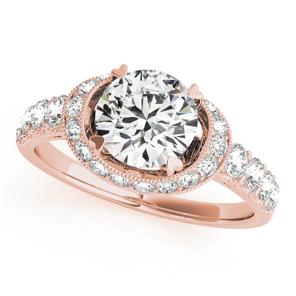 A 4 pronged curved halo diamond engagement ring in rose gold with a round cut stone on a scallop setting embedded with melee diamonds.