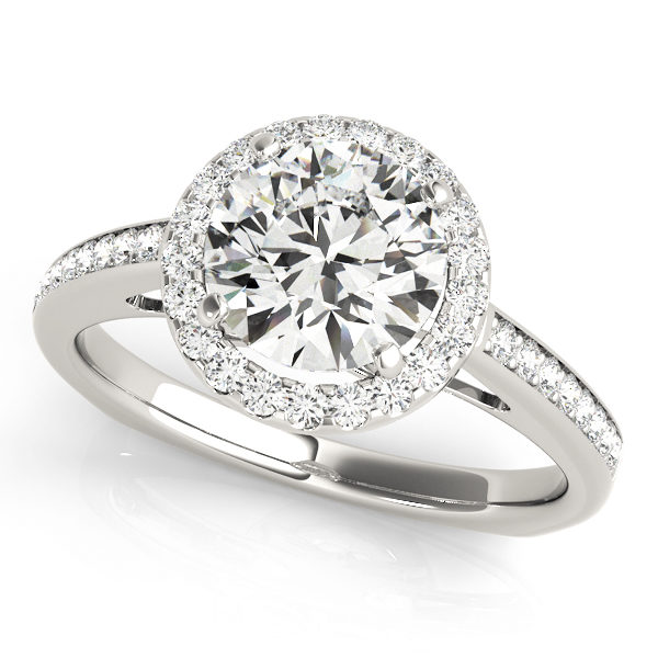 A 4 pronged halo diamond engagement ring in white gold with a round cut stone with a white gold open cathedral band and a paved setting embedded with melee diamonds.