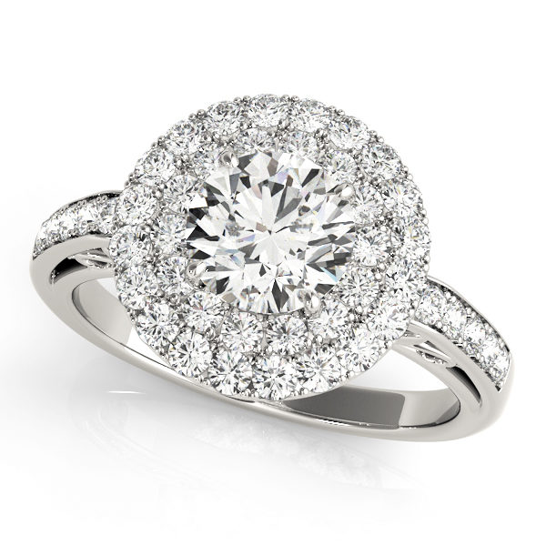 A halo engagement diamond ring in white gold with a round cut and a channel setting encrusted with melee diamonds.