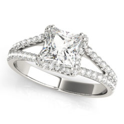 An engagement diamond ring in white gold with an asscher cut and a split shank encrusted with melee diamonds.
