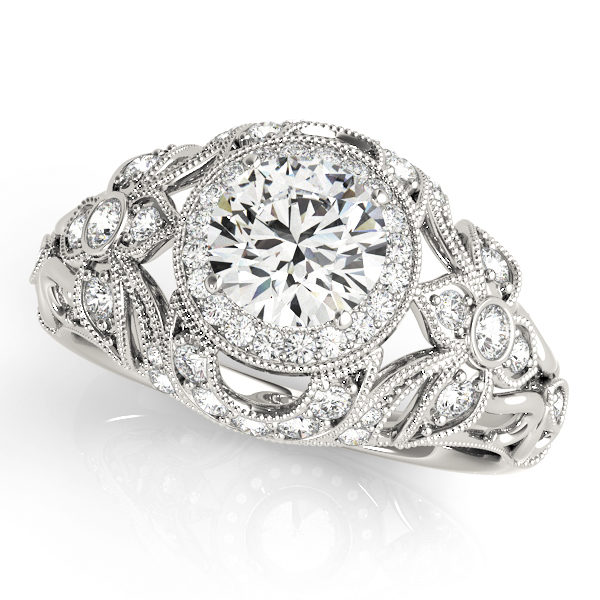 A front view of white gold flower style engagement ring with round centre cut jewel and shoulder engraved with diamonds and last a complicated tulip vintage band.
