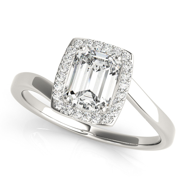 A top view of a diamond engagement ring, with an emerald cut centre jewel surrounded by a halo of diamonds, and a bypass style pale silver band.