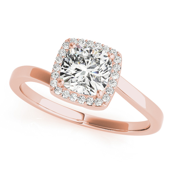 The slanted view of a rose gold diamond engagement ring, that's halo set held together by four prongs, and a twisted bypass style band made also of rose gold.
