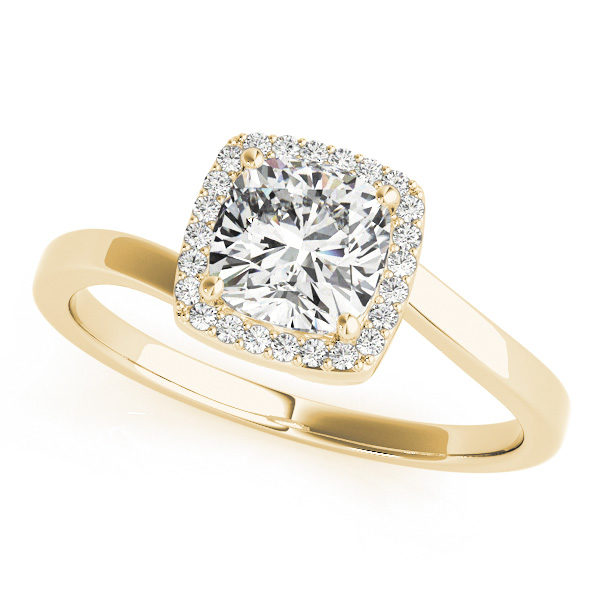 The slanted view of a yellow gold diamond engagement ring, that's halo set held together by four prongs, and a twisted bypass style band made also of yellow gold.