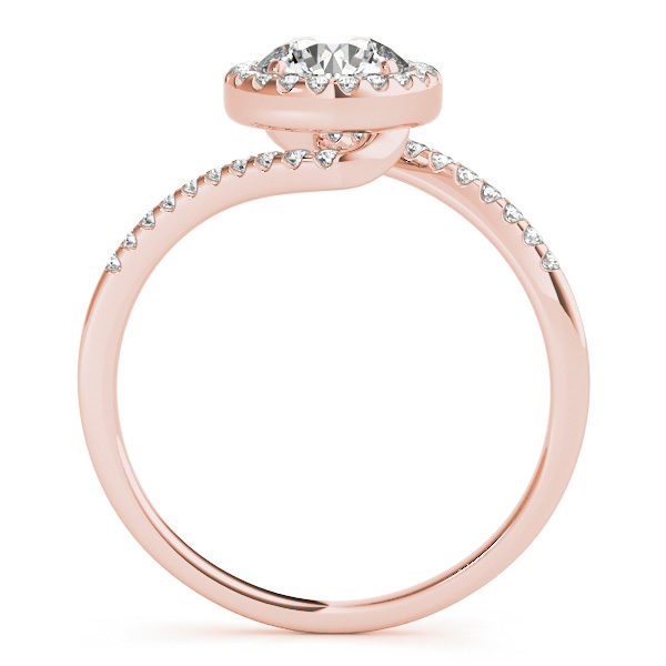 A side view of a rose gold diamond halo engagement ring, with a bypass style band decorated with small diamonds set using delicate French V splits.