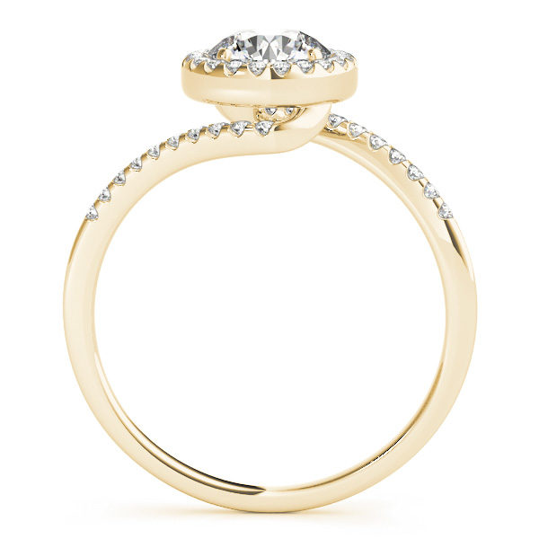 A side view of a yellow gold diamond halo engagement ring, with a bypass style band decorated with small diamonds set using delicate French V splits.