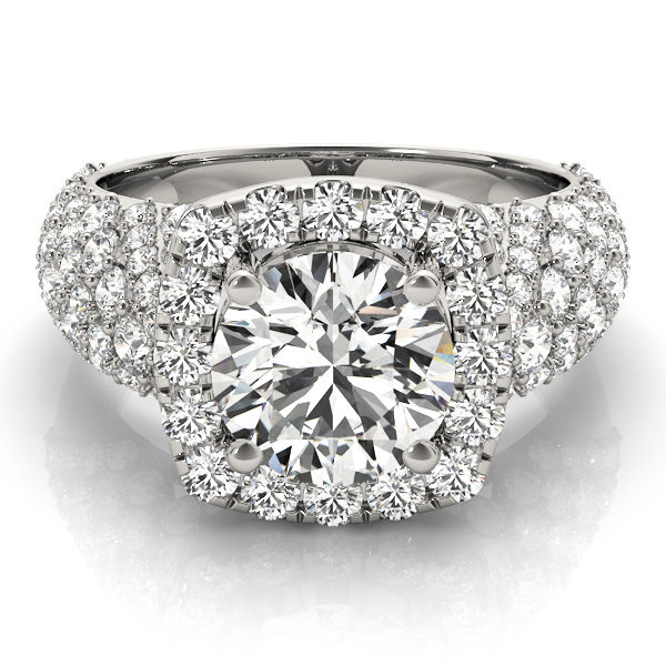 a thick band white gold diamond halo engagement ring surrounded by smaller diamonds also on each shoulder
