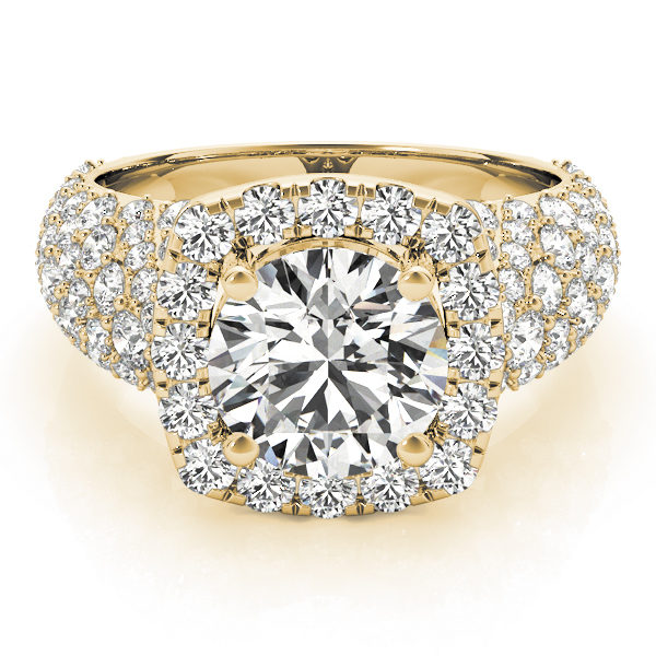 a thick band yellow gold diamond halo engagement ring surrounded by smaller diamonds also on each shoulder