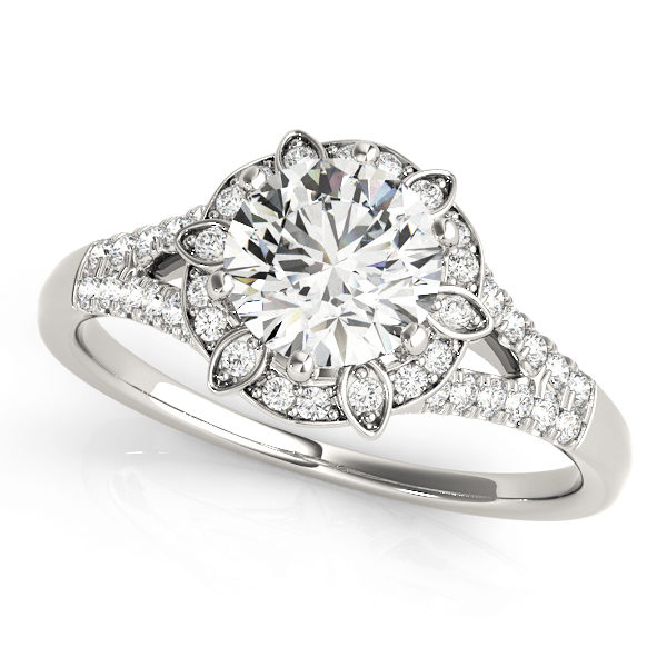 a petite white gold diamond halo engagement ring surrounded by smaller diamonds on each of the split shanks