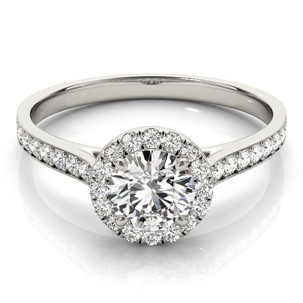Top view of a white-gold halo engagement ring with a large diamond on top with small diamonds surrounding it and also along the band