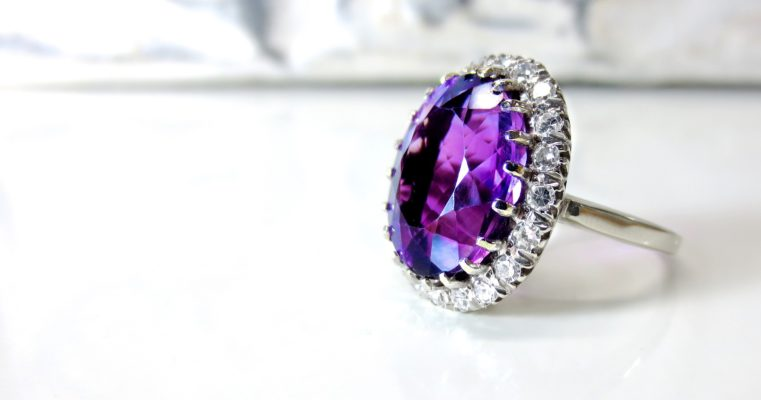 Diamond facts for a round cut amethyst diamond ring with accent stones on a white space