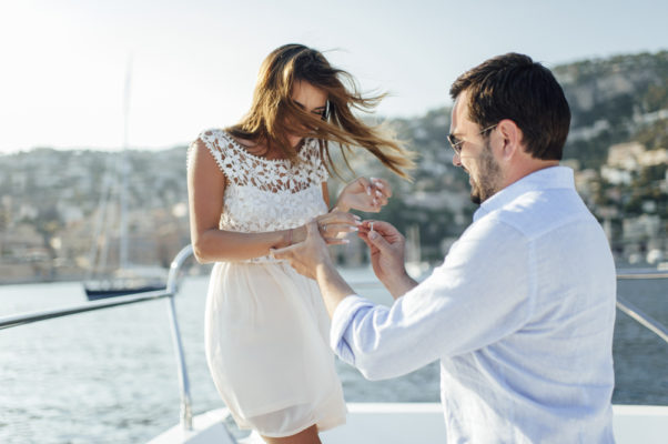 A yatch marrige proposal with an engagement ring styles of a man in white polo wears a woman in white dress an engagement ring into her finger ring